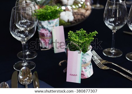 Elegant table setting with selaginella plants as party favors. Watercolor place cards in delicate pastel color palette. Natural light, shallow depth of field. - stock photo