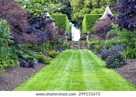Elegant, traditional landscaped garden with lush green lawn leading to stone stairs, with mature herbs, flowers, shrubs, trees and topiary hedge on both sides of a grassy path - stock photo