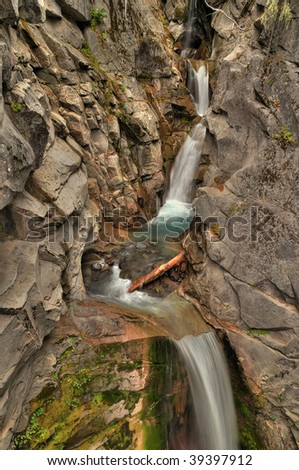 Elegant upper Christine falls flowing through rocky terrain in multiple tiers at Mount Rainier National Park during autumn - stock photo