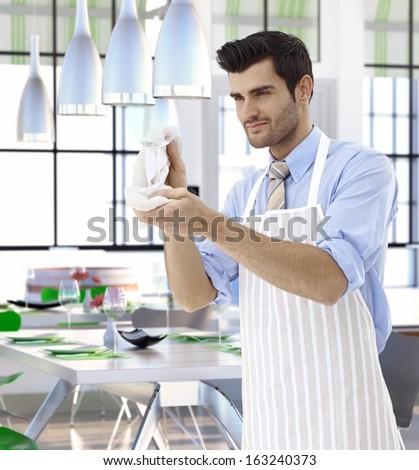 Elegant waiter cleaning wineglass at restaurant. - stock photo