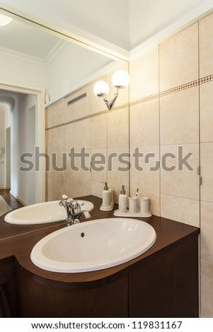 Elegant washbasin and huge mirror in stylish bathroom - stock photo