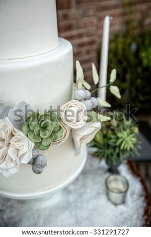 Elegant wedding cake with sugar flowers and succulents - stock photo