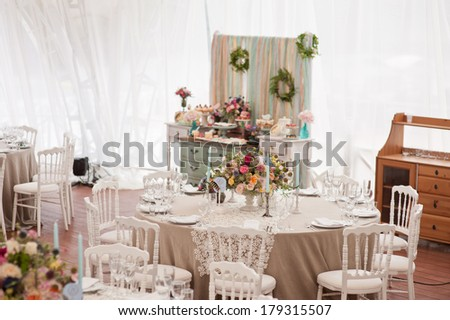 Elegant wedding reception area, ready for guests and the bridal party. Rich bunch of flowers table. - stock photo
