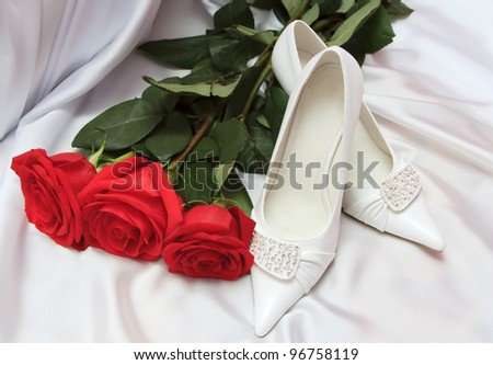 Elegant wedding shoes with red roses - stock photo