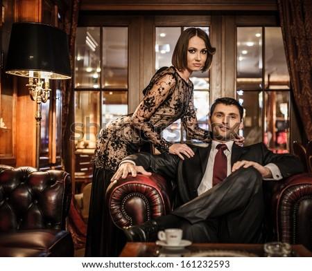 Elegant well-dressed couple in luxury interior - stock photo
