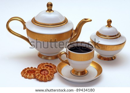 Elegant white and gold tea service with cookies - stock photo
