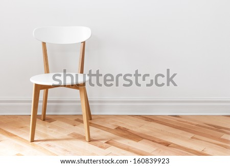 Elegant white chair in an empty room with wooden floor. - stock photo