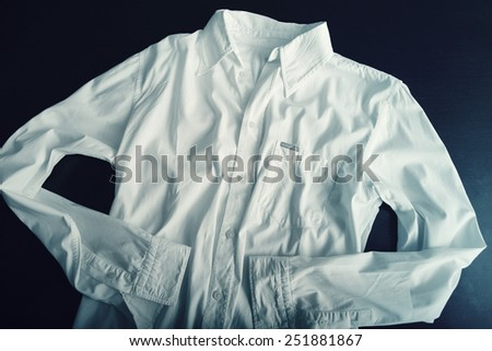 Elegant white shirt on table. Dark scene. - stock photo
