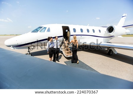 Elegant woman boarding private jet with airhostess and pilot at airport terminal - stock photo