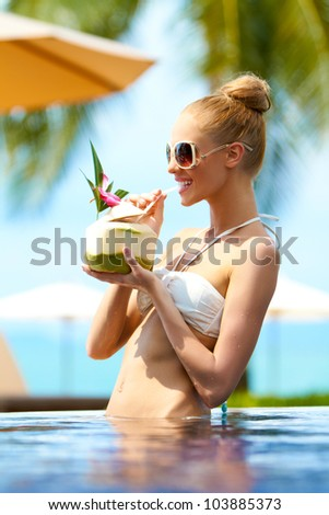 Elegant woman in a bikini and sunglasses standing in a pool drinking a cocktail at a tropical resort - stock photo