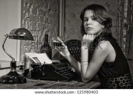 Elegant woman in black at the table with the old typewriter - stock photo