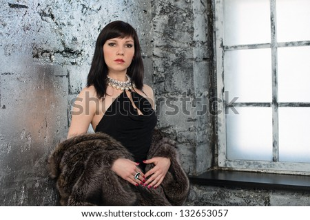 Elegant woman in black dress and fur coat standing by the window - stock photo