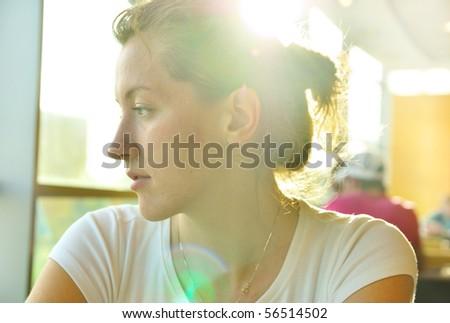elegant woman in cafe is looking sideways - stock photo