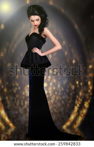 Elegant woman in evening black dress on a gold background. gorgeous brunette - stock photo