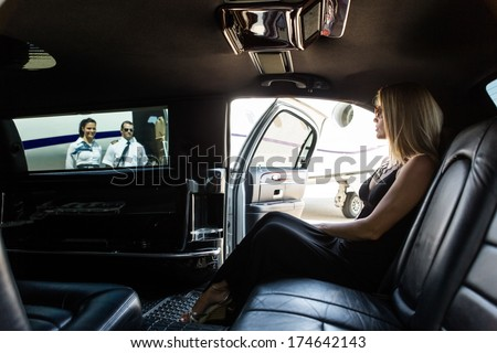Elegant woman in limousine with airhostess and pilot near private jet at terminal - stock photo