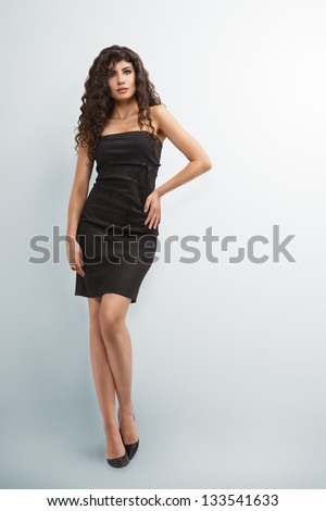 Elegant woman in little black dress with long curly hair - stock photo
