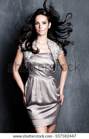 elegant woman in silver dress with long black flying hair studio shot - stock photo
