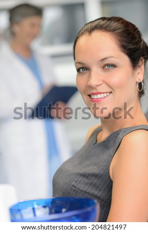 Elegant woman patient at dental surgery smiling dentist in background - stock photo