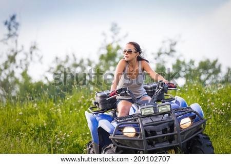 Elegant woman riding quadrocycle - stock photo