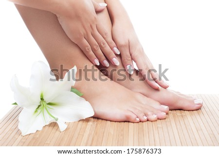 Elegant woman's manicured hand and pedicured feet with madonna lily on bamboo mat - stock photo