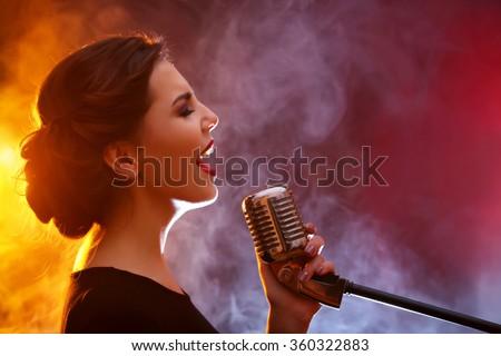 Elegant woman singing in colourful smoke, close up - stock photo