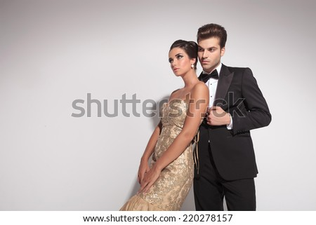 Elegant woman wearing a golden dress leaning on her lover, both looking away. On grey studion background. - stock photo