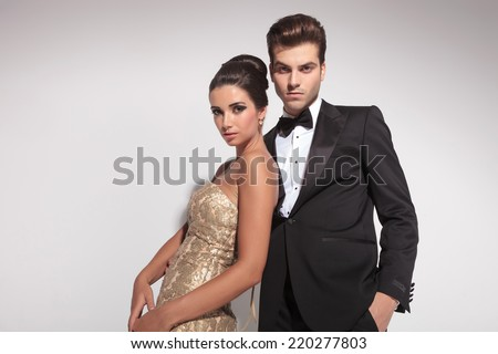 Elegant woman wearing a golden dress leaning on her lover while he is embracing her, both looking at the camera. On grey background. - stock photo