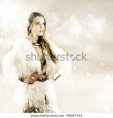 elegant woman wearing fur coat with hands on hips, with snow falling around her in a winter weather concept - stock photo