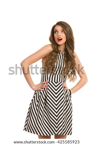 Elegant woman with long brown hair wearing black and white striped dress posing with hands on hip and looking up, Three quarter length studio shot isolated on white. - stock photo