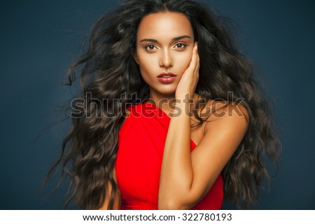 Elegant woman with long wavy hair and red lips wearing red dress . Fashion and cosmetics studio shot, Horizontal - stock photo