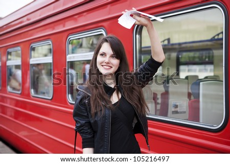 Elegant woman with suitcase standing on the platform of a train station - stock photo