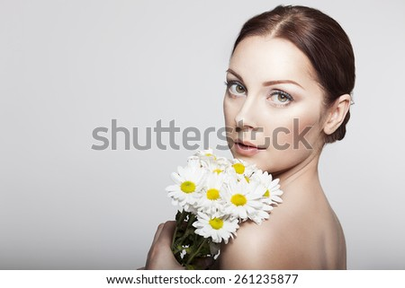 Elegant Womanl With Camomile Flowers.Close-up Beauty Woman Face. Perfect Skin.Body care. Professional Make-up. - stock photo