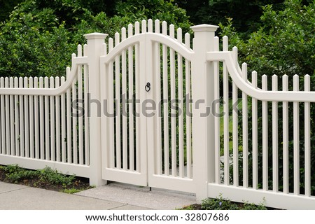Elegant wooden gate and fence on house entrance - stock photo