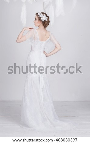 Elegant young and dreamy beautiful bride in a luxurious lace wedding dress. She has lace decoration in her beautiful dark blond hair. She is elegant and delicate. The dress has lacing on the back. - stock photo