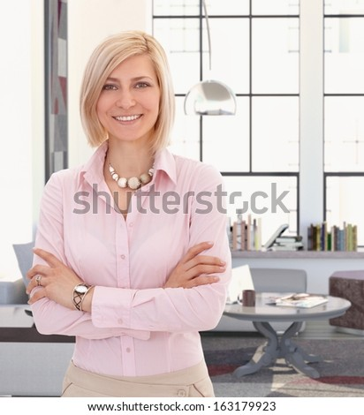 Elegant young blond woman at home, looking at camera smiling. - stock photo
