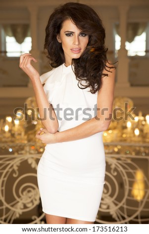 Elegant young brunette woman posing in fashionable white dress, looking at camera. - stock photo
