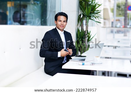Elegant young businessman button his suit jacket, elegant business man closing his suit jacket sitting in modern place at work break, success concept - stock photo