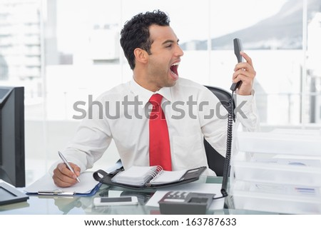 Elegant young businessman shouting as he holds out phone at a bright office - stock photo