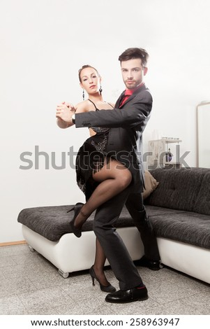 Elegant young couple dancing at home - stock photo