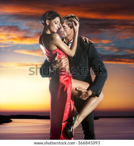 Elegant young couple in love posing against sea at sunset  - stock photo