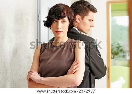 elegant, young couple standing back to back in a room - stock photo