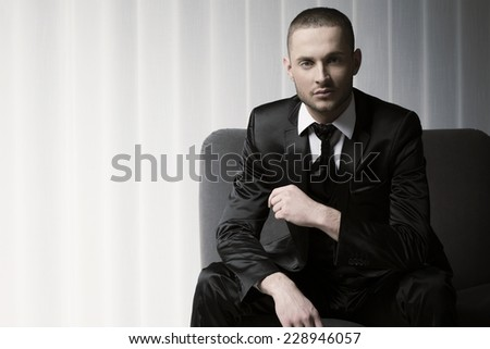 elegant young fashion man in tuxedo on a sofa, blinds background - stock photo