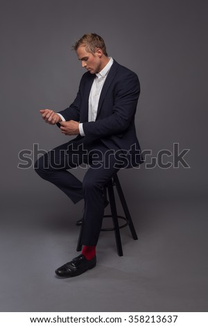 elegant young fashion man in tuxedo sitting on the chair - stock photo