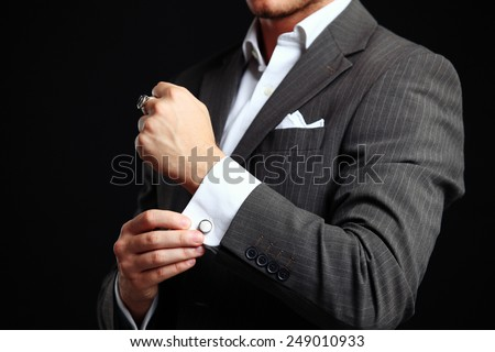 elegant young fashion man looking at his cufflinks while fixing them - stock photo