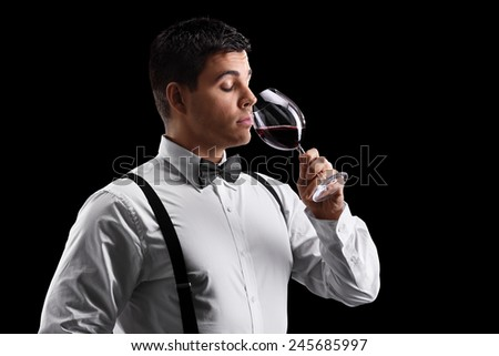 Elegant young guy drinking wine on black background - stock photo