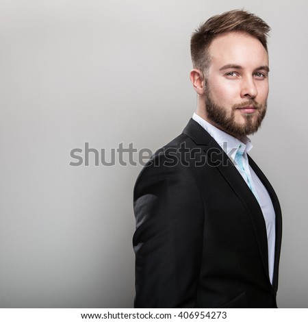 Elegant young handsome bearded man in classic black costume & white shirt. - stock photo