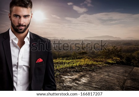 Elegant young handsome man in black costume pose on tropical view point. - stock photo