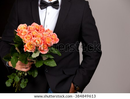 Elegant young handsome man in black suit with bouquet of roses.  - stock photo