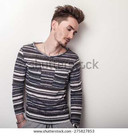 Elegant young handsome man in bright striped gray t-shirt. Studio fashion portrait.  - stock photo