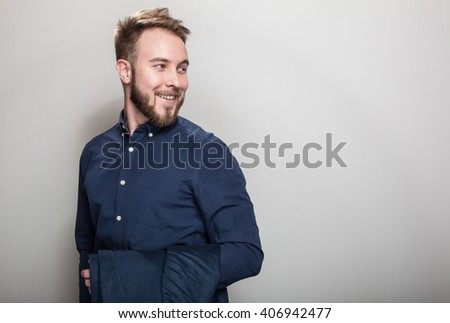 Elegant young handsome man in dark blue classic shirt and jacket on his shoulder. Studio fashion portrait. - stock photo